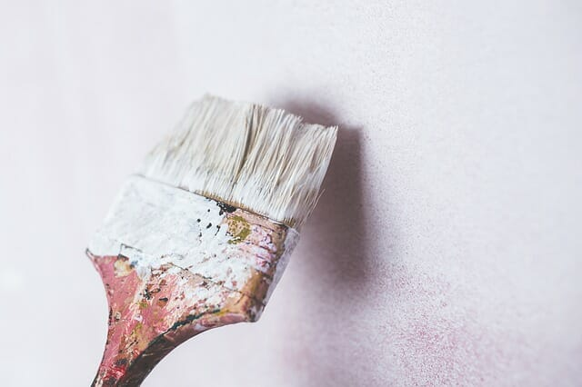 painting the wall with a brush