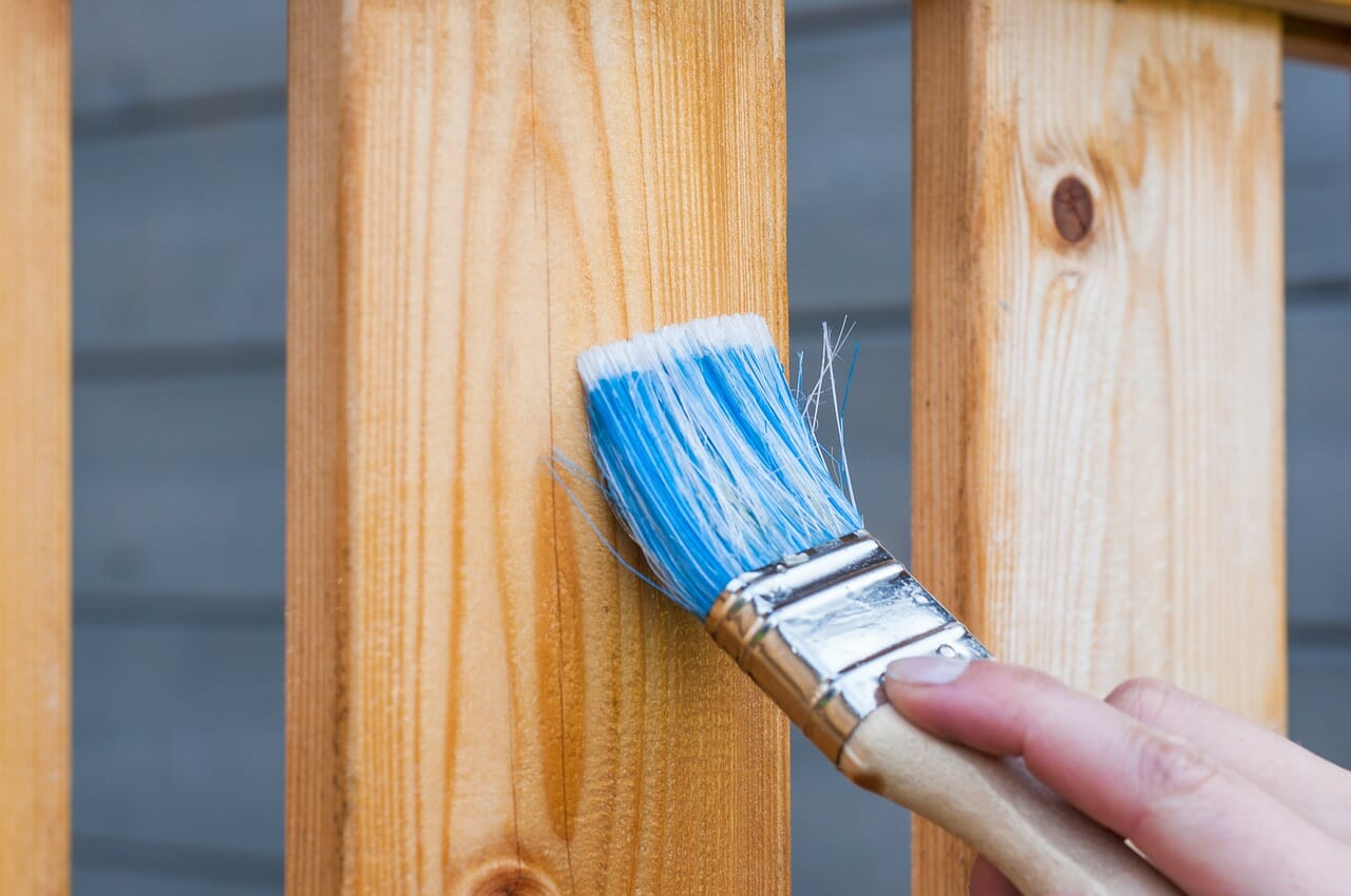 a paint brush being used on a wooden slat