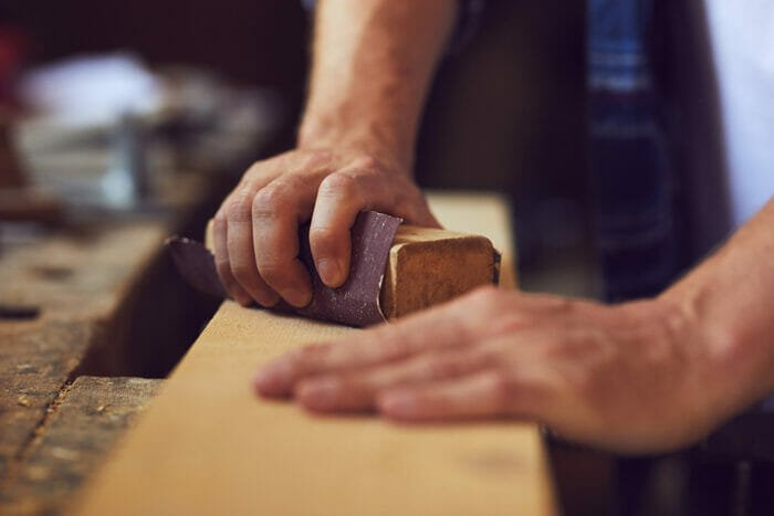 Close-up of carpenter using sandpaper on a wooden plank in a carpentry shop