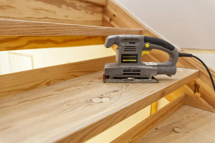 closeup of a sheet sander sitting idle on a wooden staircase