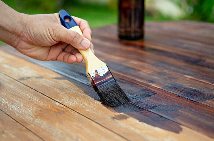 a man painting over stained wood using a paint brush