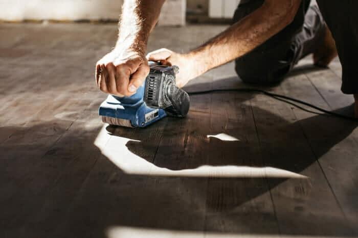 a man sanding a hardwood floor using an orbital sander