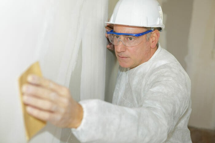contractor sanding the drywall whilst wearing safety goggles