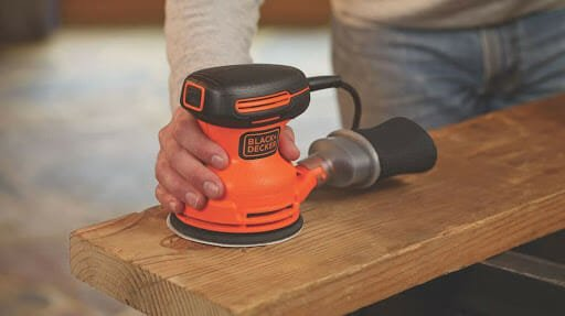 finishing a wooden cabinet using a palm sander