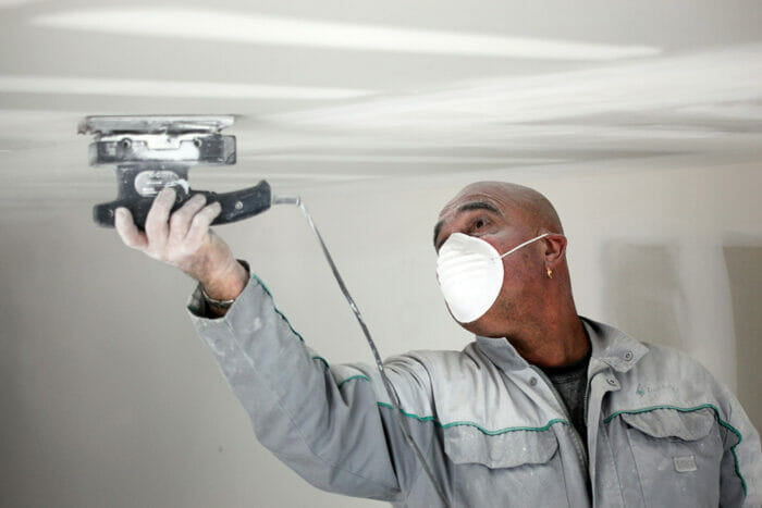 man sanding a drywall ceiling whilst wearing a face mask