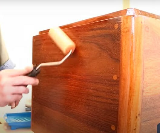 using a roller to apply varnish to your cabinet after sanding it down with an orbital sander