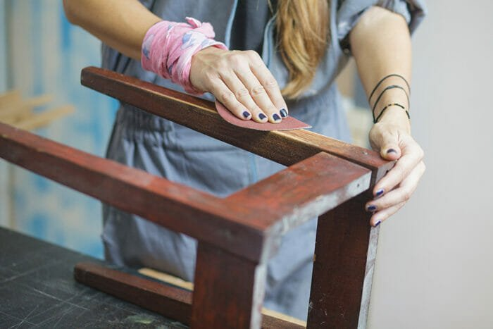 woman sanding a wooden table by hand