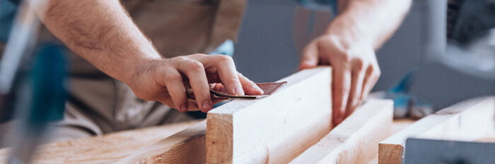 a carpenter sanding a length of wood by hand