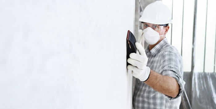construction worker wearing a mask whilst sanding drywall