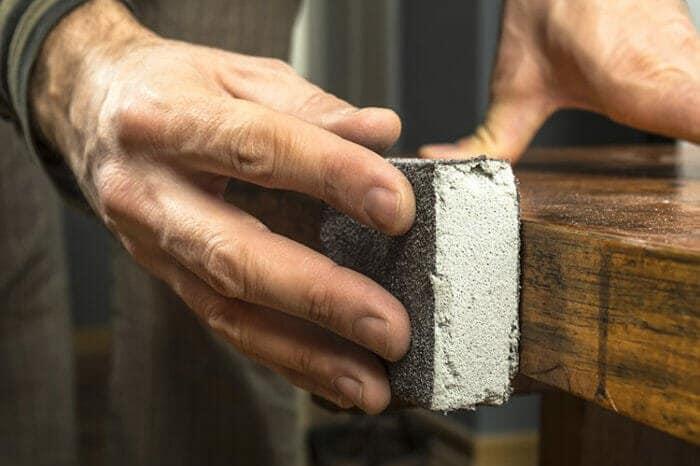 Closeup of Handyman finish sanding a cabinet by hand