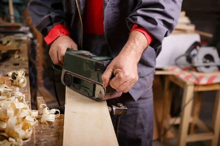 belt sander being used in a workshop to sand wood