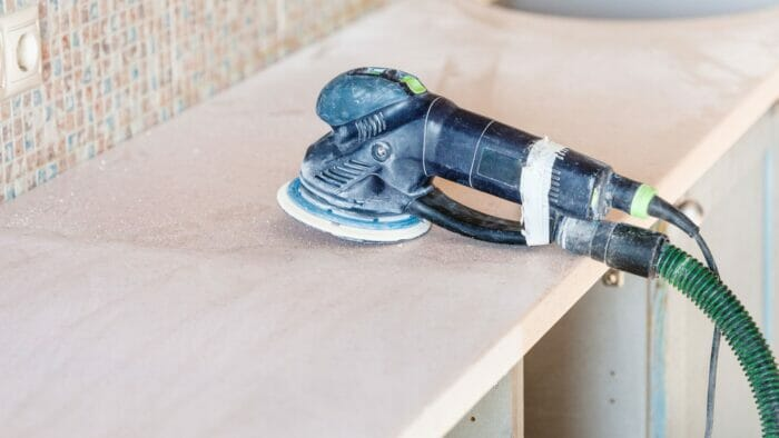 an orbital sander being used to remove water stains from wood