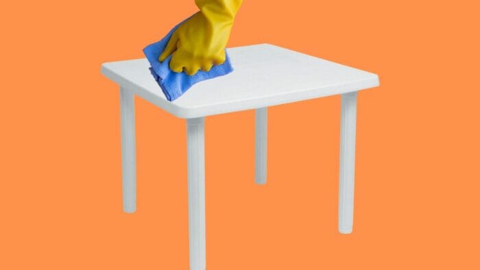 closeup of a plastic table being wiped down with a cloth prior to painting
